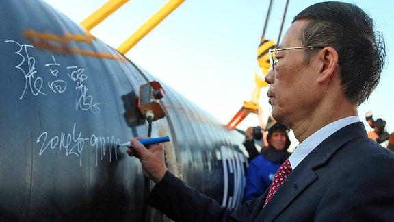 Chinas Vizepremier Zhang Gaoli unterschreibt auf einem Pipeline-Rohr.