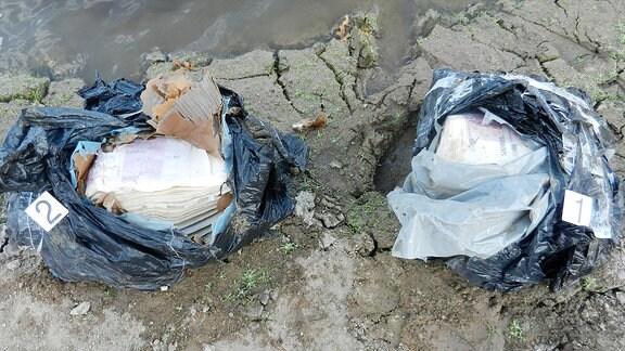 Zwei Mülltüten liegen am See.
