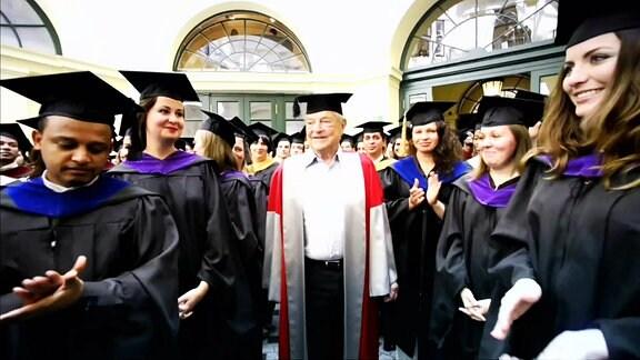 George Soros mit Akademikerhut inmitten von Absolventen der CEU in Budapest