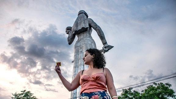 Frau vor Frauenstatur mit Kondom in der Hand