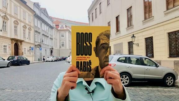 """Helena Sulcova hält ein Buch mit dem Titel """"The Boss"""" hoch"""