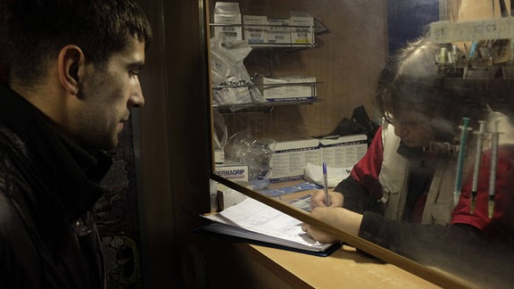 Ein Heroinsüchtigen tauscht Spritzen an einem Nadelaustausch Schreibtisch in St.Petersburg, Russland.