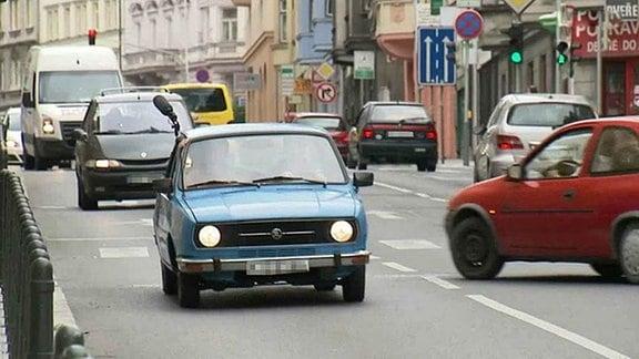 Ein blauer Skoda 120 fährt durch eine Stadt