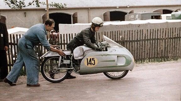 Ein Mechaniker hilft Ernst Degner auf dem Weg zum Vorstart.