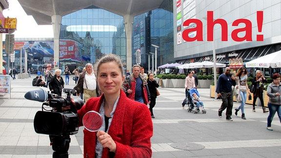 Eine Redakteurin mit Kamera in einer Fußgängerzone.