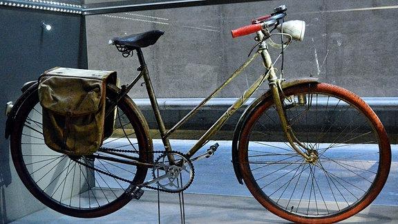 Ein altes Fahrrad mit Gepäcktaschen und roten Lenkergriffen als Ausstellungsstück.