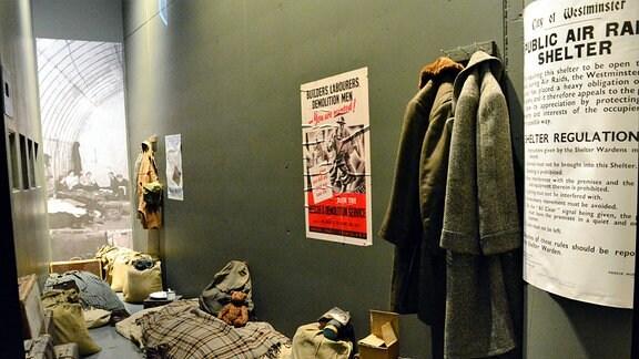 Eine Schlafstätte mit Plakaten an der Wand. Zwei Mäntel hängen am Haken.