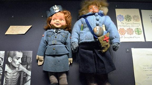 Zwei alte Puppen auf einem Tisch. Auch ein Bild eines ausgemergelten jungen Menschens ist zu sehen.