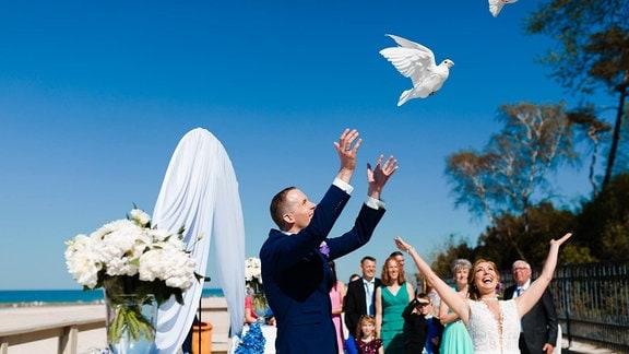 Ein Brautpaar lässt Tauben fliegen.