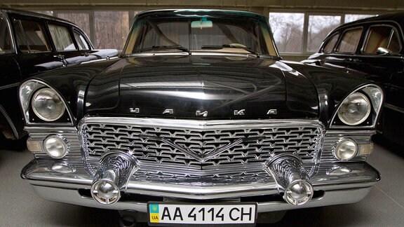 Ein altes Automobil neben weiteren in einer Garage.