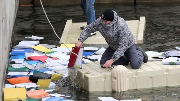Menschen fischen verschiedene Dokumente und Unterlagen aus einem See.