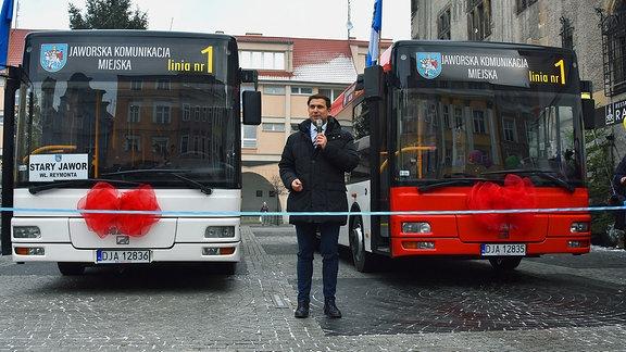 Ein Mann steht mit einem Mikrofon in der Hand vor zwei Bussen, vor die ein blaues Band gespannt ist.