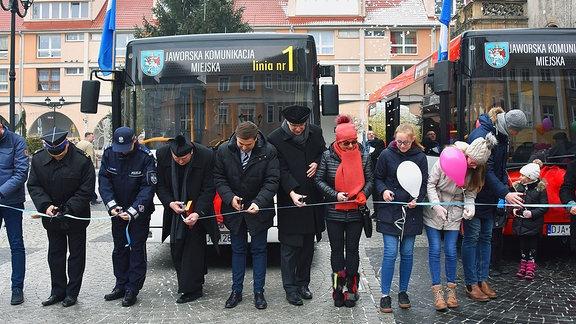 Menschen durschneiden ein Band, dass vor zwei Bussen gespannt ist.