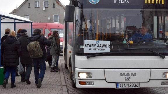 Menschen steigen in einen Bus