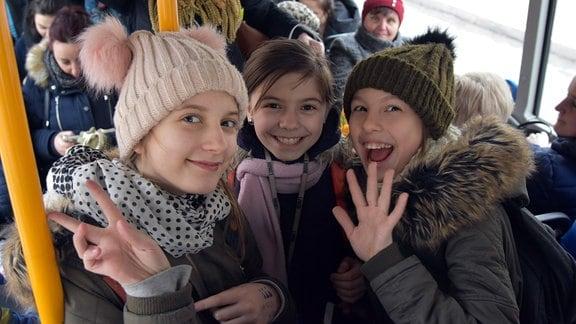 Drei Mädchen stehen in einem Bus und winken