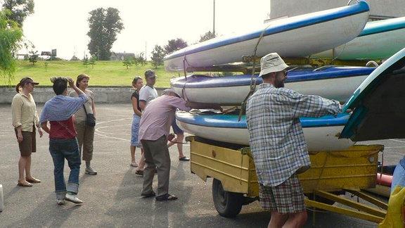 Eine Gruppe Menschen beim verladen von Kanus.