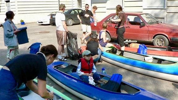 Eine Gruppe Kanufahrer beim auspacken.