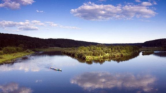 Gruppe von Kanufahrern auf einem Fluss vor grünem Wald.