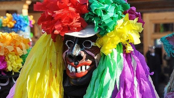 Ein maskierter Karnevalist mit bunten Tüchern bei einem Straßenumzug.