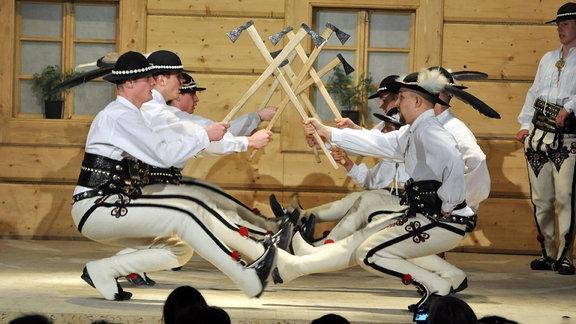 Gorale in typischen Trachten und mit Äxten zeigen einen Tanz auf einer Bühne.
