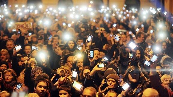 Viele Menschen halten ihr Smartphone hoch.