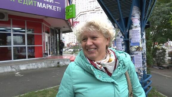 Eine Frau schaut lächelnd in Richtung Kamera.