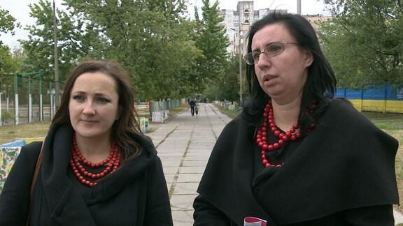 Zwei Frauen stehen auf einem Gehweg und schauen zu dem sie fragenden Reporter.
