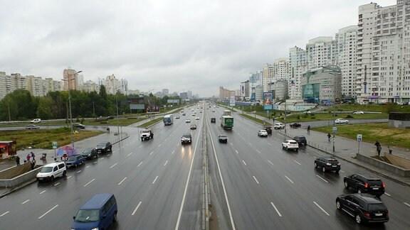 Eine mehrspurige Autobahn, gesäumt von Plattenbauten.