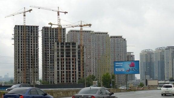 Plattenbauten in Kiew, davor werden weitere Neubauten hochgezogen. mehrere Kräne stehen neben den Häusern.