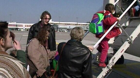 Menschen besteigen ein Flugzeug
