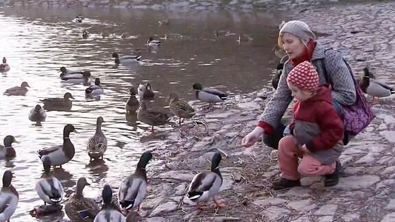Mutter mit Kind am Wasser.