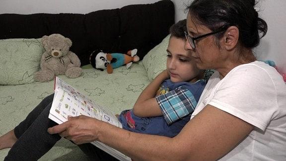 Eine Frau liest mit einem Jungen in einem Buch