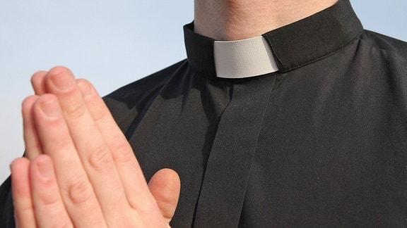 Ein Priester faltet die Hände