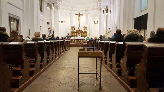 Menschen sitzen, mit Blick auf den Altar, links und rechts des Ganges in Kirchenbänken.