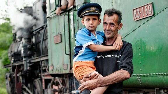 Arbeiter mit Sohn auf dem Arm vor alter Damplokomotive in Bosnien.