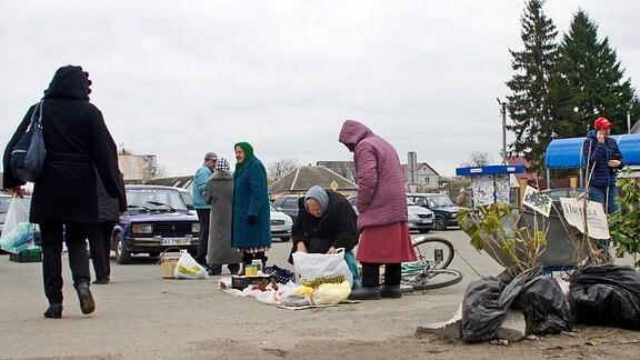 Straßenverkäuferinnen auf einem Parkplatz in der Kleinstadt Dymerka.