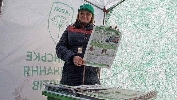 Wahlhelferin mit Wahlzeitung im Ort Schaschkiw, Ukraine.