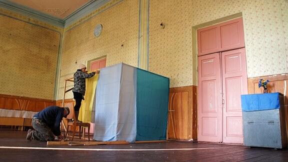 Wahlhelfer bauen Kabinen im Gemeindehaus des Dorfes Marijka auf.
