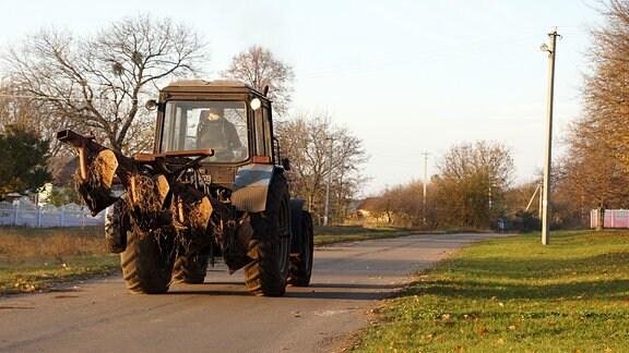 Traktor auf einer Straße im Dorf Marijka, Ukraine.
