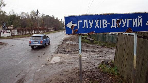 Alter Kombi auf einer schlammigen Landstraße im Dorf Lutiwka. Davor ein Straßenschild nach «Gluchiw-Drugij».