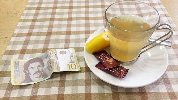 10-Dinar-Schein an Teetasse