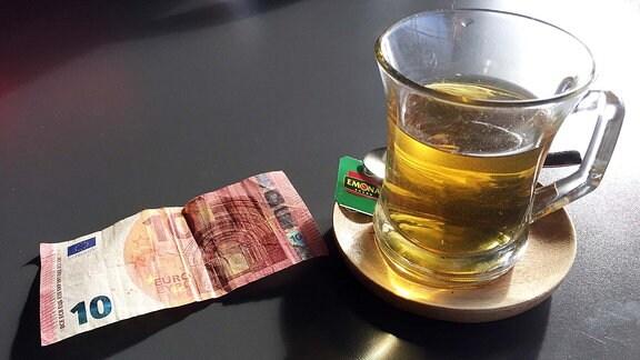 10-Euro-Schein an Teetasse