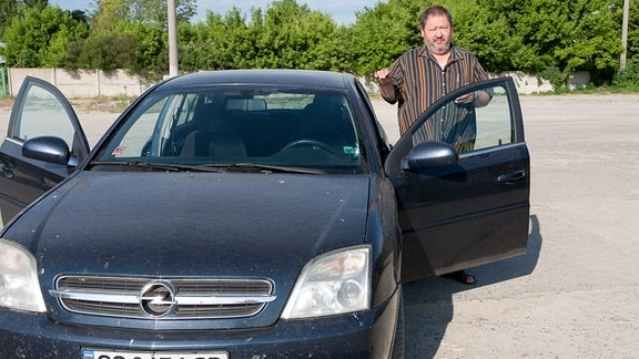 Ein Mann neben einem Auto