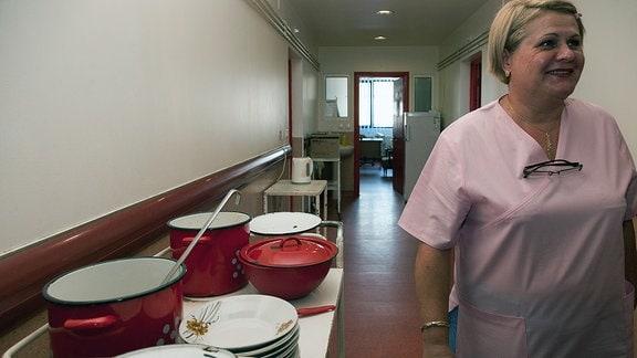 Eine Frau läuft an Töpfen und Tellern im Stationsflur vorbei
