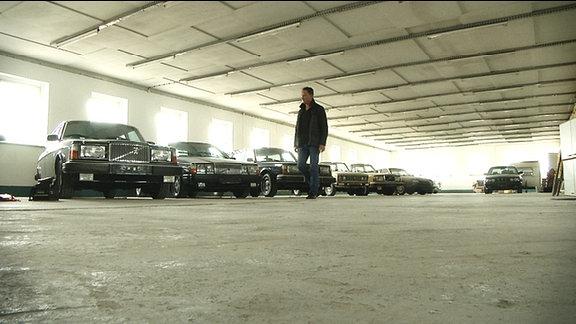 Ein Mann geht durch ein Parkhaus mit alten Autos