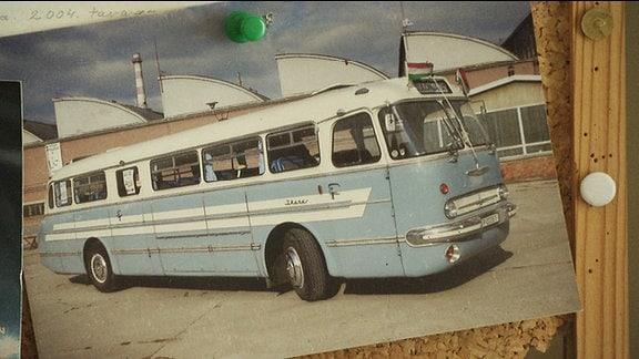Das Foto eines alten Busses ist an eine Wand gepinnt