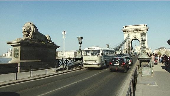 Ein alter Bus fährt über eine Brücke