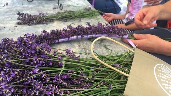 Auf einem Tisch liegen lose Lavendelzweige die zu Sträcuhern gebunden werden.