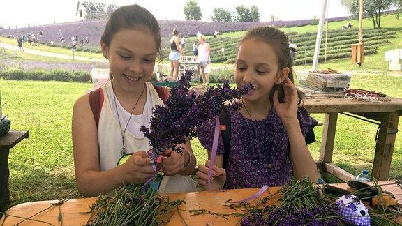 Zwei Mädchen sitzen an einem Tisch und binden einen Lavendelstrauch.