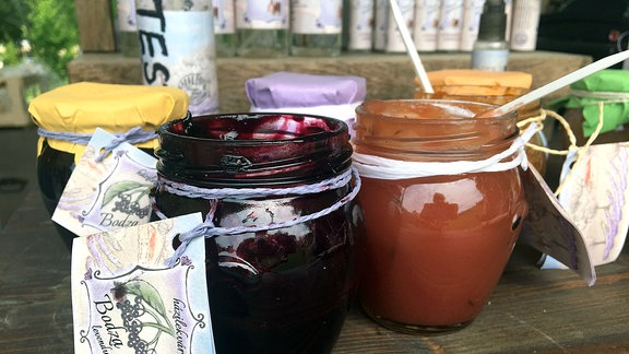 Mehrere Gläser mit verschiedener Marmelade stehen auf einem Tisch.